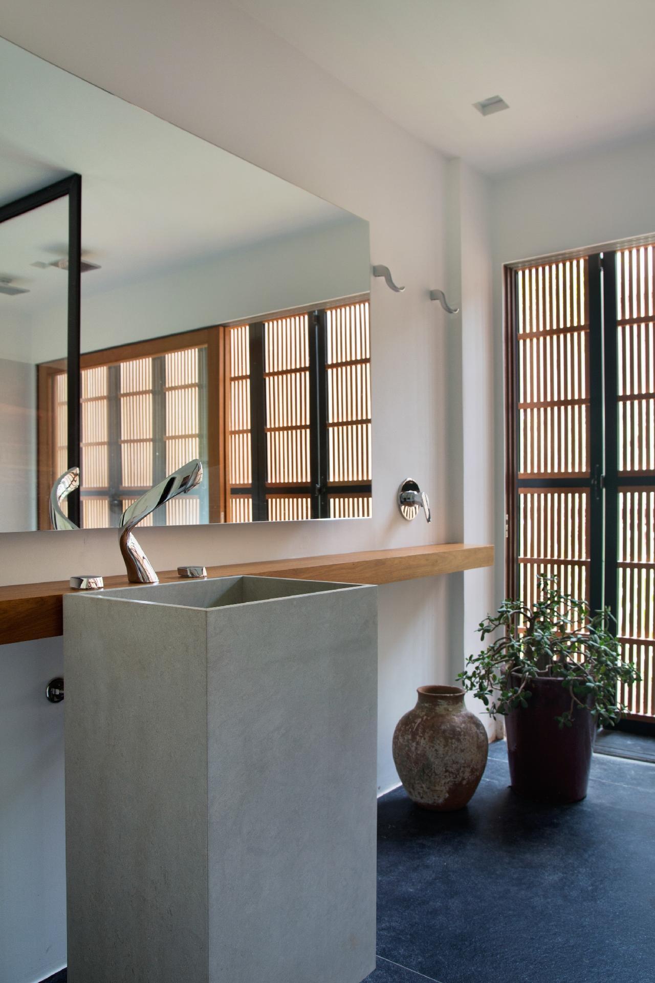 O banheiro social tem uma decoração leve e contemporânea. A bancada estreita de madeira acompanha uma cuba de piso, com aspecto cimentício. A casa de campo assinada pelo arquiteto Otto Felix fica em Campinas (SP)