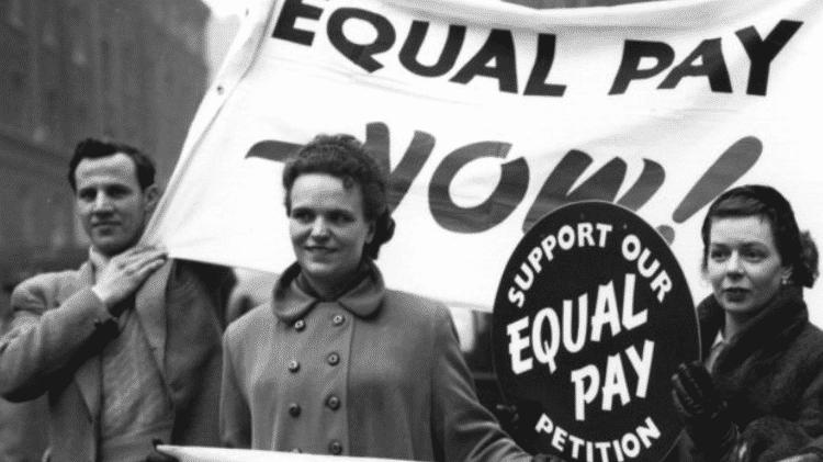 Esse debate tem acontecido há décadas, como na foto, em que ativistas por pagamento igual pedem apoio a uma petição em Londres em 1954 - Getty Images - Getty Images