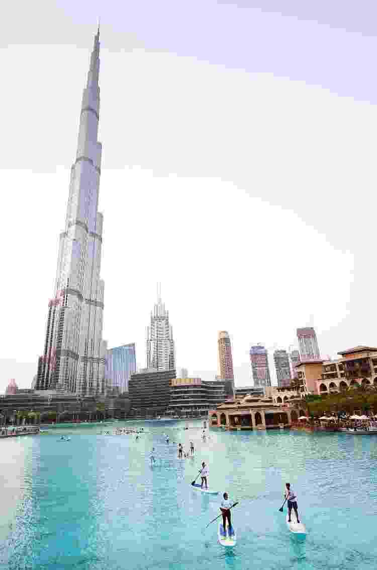 Pessoas praticam stand-up paddle ao lado do Burj Khalifa - Getty Images - Getty Images