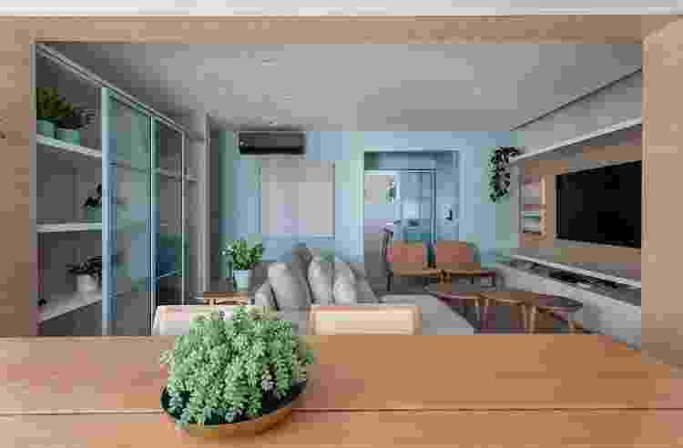 Nesta sala, uma mesa foi capaz de ocupar o espaço na retaguarda do sofá. Com uma solução fácil e prática, a arquiteta mostra que o menos é mais nestas situações - Evelyn Muller - Evelyn Muller