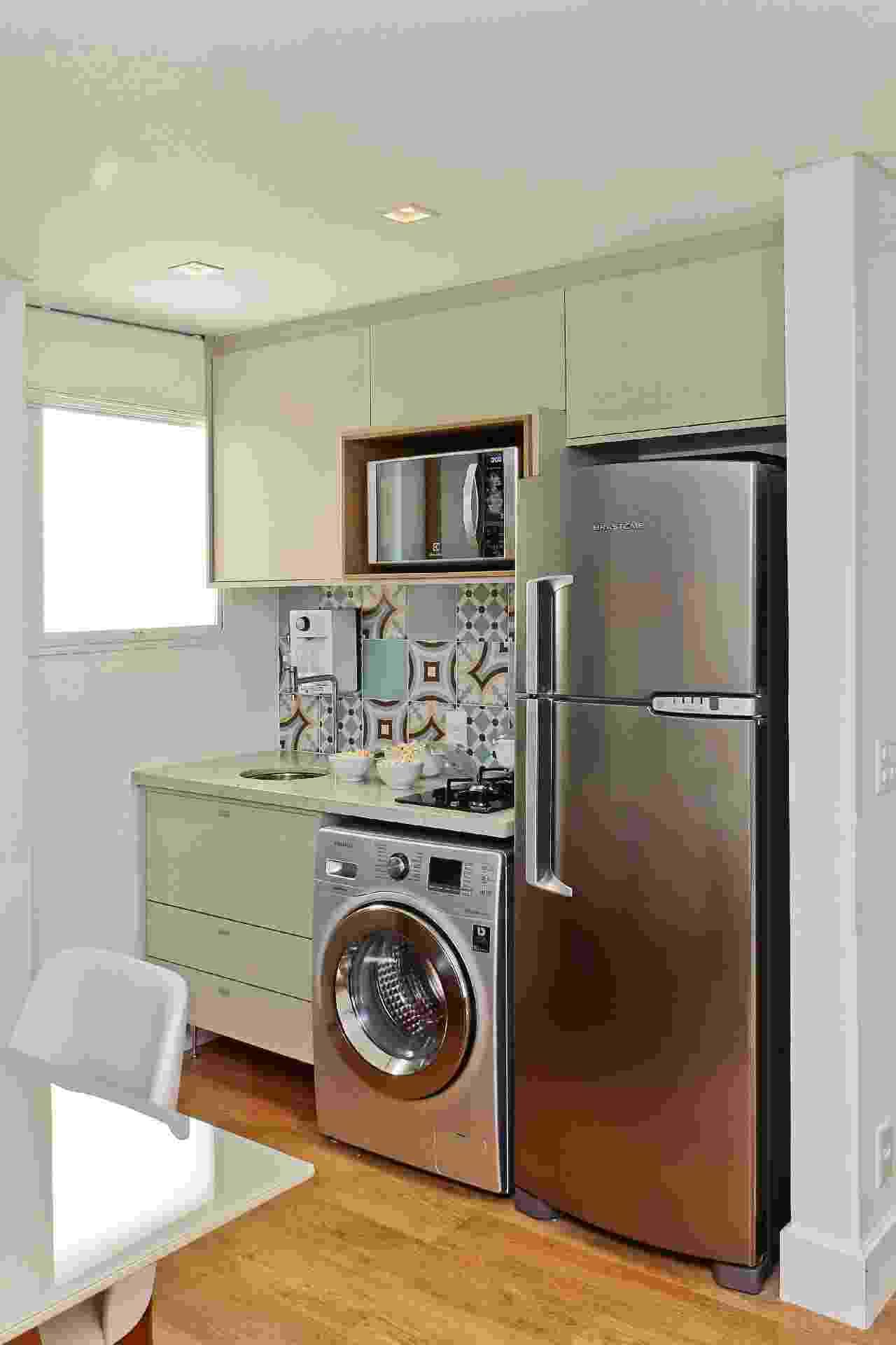 Neste pequeno apartamento, a cozinha não só reúne cooktop e pia, com medidas compactas, como também abrigou a lava-roupas, pois não há lavanderia. Tudo milimetricamente calculado pela Figoli-Ravecca, que ainda desenhou a marcenaria com lugar para micro-ondas. - Eder Lizier