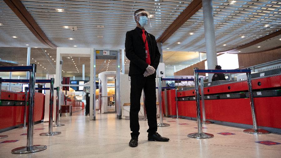 Segurança usa proteção contra coronavírus na entrada de embarque do aeroporto Charles De Gaulle; voos entre França e Brasil permanecerão suspensos até 19 de abril - Getty Images