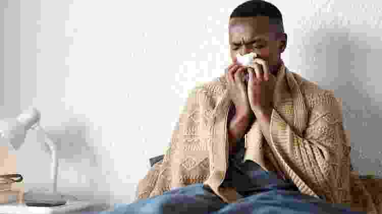 homem resfriado assoando o nariz - iStock - iStock