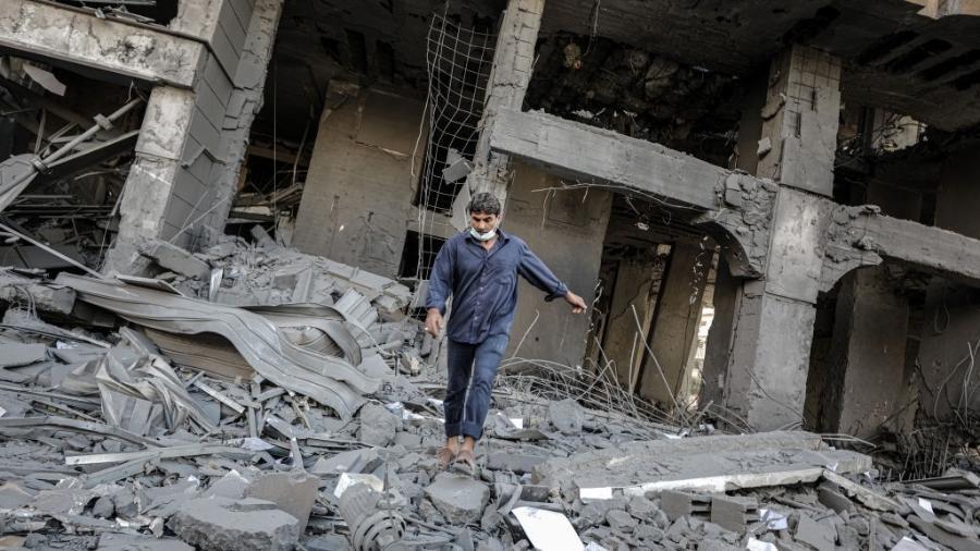 Pessoas inspecionam as ruínas de um prédio demolido depois que aviões de guerra israelenses realizaram ataques aéreos na Cidade de Gaza, Gaza em 12 de maio de 2021 - Getty Images