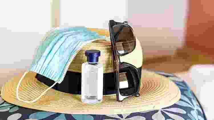 chapéu de praia com máscara e álcool em gel viagem covid - Getty Images/iStockphoto - Getty Images/iStockphoto