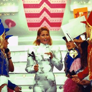 """Xuxa desce da nave do """"Xou da Xuxa"""" veste traje colado com detalhes metalizados e canta com as Paquitas - Reprodução/Memória Globo"""