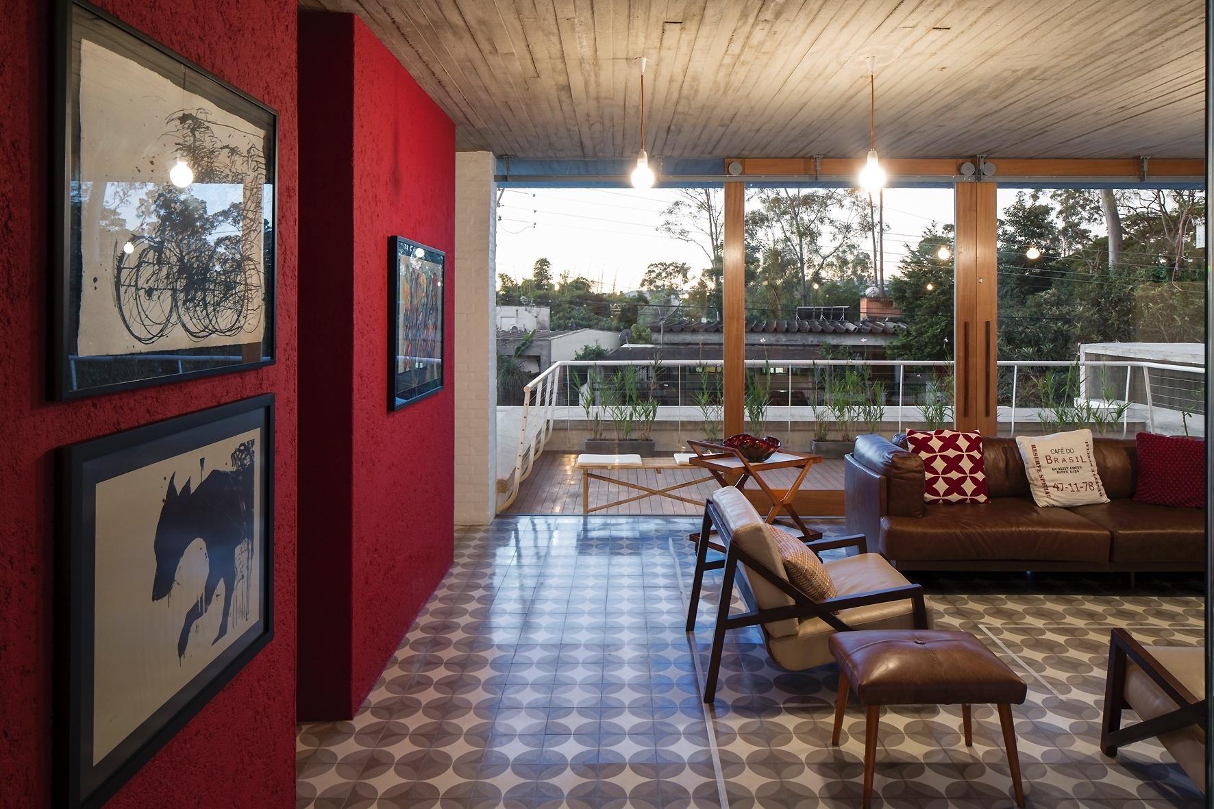 Na sala de estar, a parede com pintura vermelha e textura rústica contrasta com o teto em concreto e o piso de ladrilhos hidráulicos, ambos em tons de cinza. O ambiente recebe luz natural graças aos fechamentos de vidro e às portas de correr  que se abrem para o terraço. A casa Lapa é um projeto do escritório Brasil Arquitetura