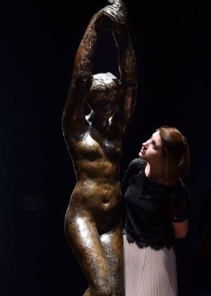 """Mulher posa ao lado da escultura """"Afrodite"""", de Auguste Rodin - Ben Stansall/AFP"""