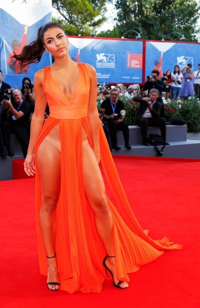 3.set.2016 - A modelo italiana Giulia Salemi também ousou em Veneza ao usar um vestido laranja com duas fendas enormes. Assim como Dayane Mello, dispensou a calcinha