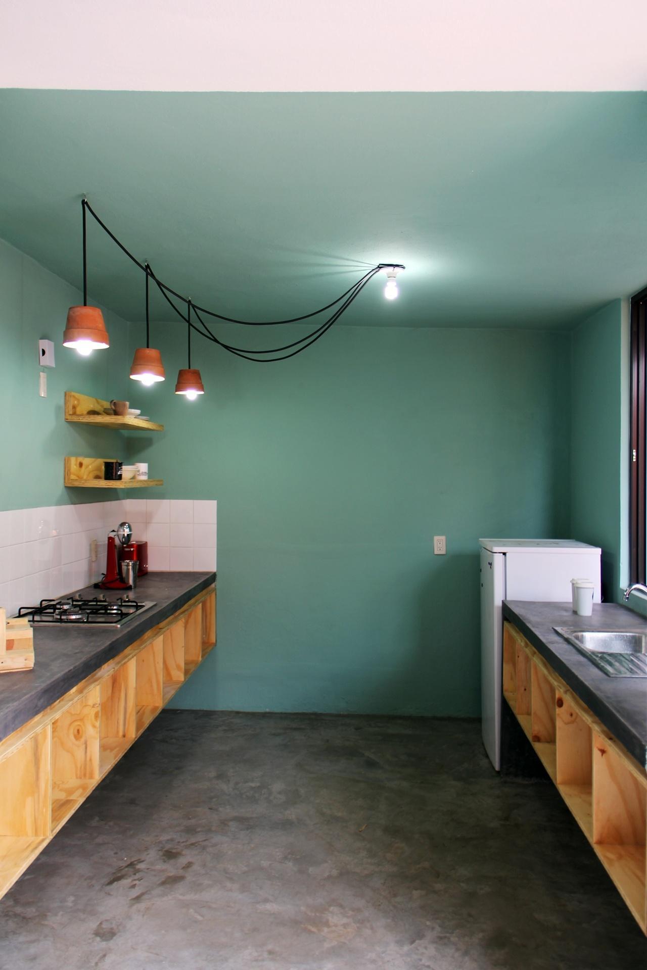 A cozinha dialoga com o jantar através das cores e materais: as paredes e o forro têm o verde usado na mesa de jantar. As bancadas de concreto polido estão dispostas nas duas paredes, uma detém a pia, a outra, o 'cooktop'. Ambas apresentam nichos de madeira clara sob si, fixados à parede. O piso, como no resto da casa Tadeo, é de cimento queimado. O projeto é do escritório Apaloosa