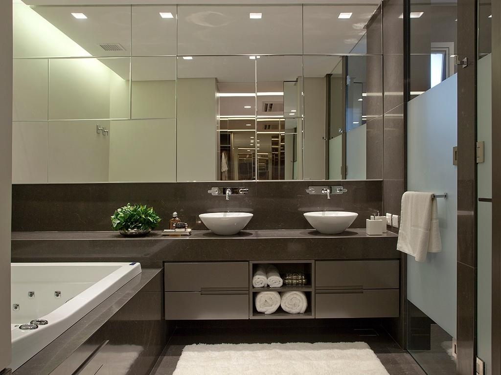 O amplo banheiro da suíte máster conta com superfícies envidraçadas, banheira e bancada de quartzo (Caesarstone)