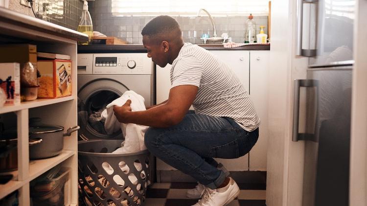 Un uomo mette il bucato nella lavatrice - Getty Images - Getty Images