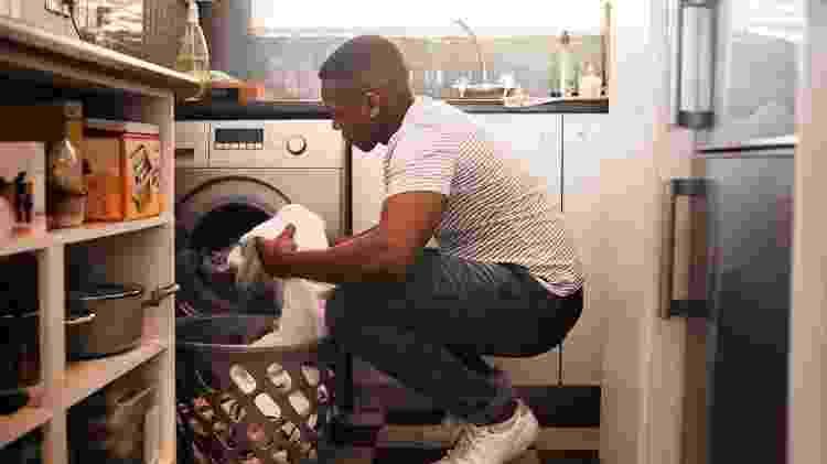 Homem colocando a roupa para lavar na máquina - Getty Images - Getty Images
