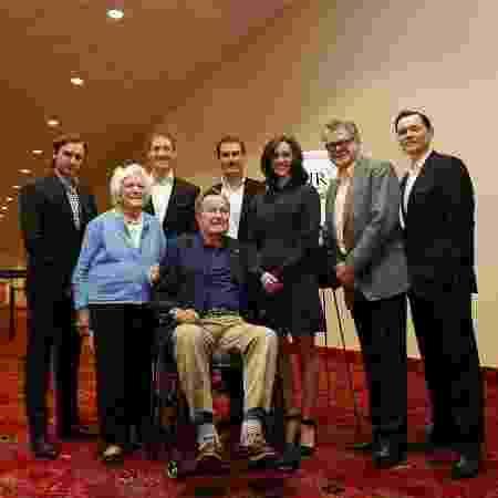 George H.W. Bush (na cadeira de rodas) teria aproveitado a foto para assediar Heather Lind (de azul, ao seu lado) em 2014  - Divulgação/AMC