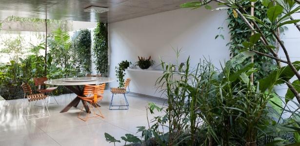 Casa encravada entre prédios preserva privacidade com jardins e recortes