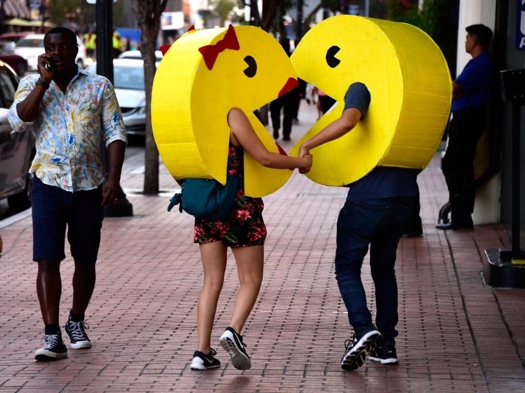 22.jul.2016 - Casal bem-humorado se fantasia de Pac-Man e caminha de mãos dadas nos arredores do Centro de Convenções de San Diego