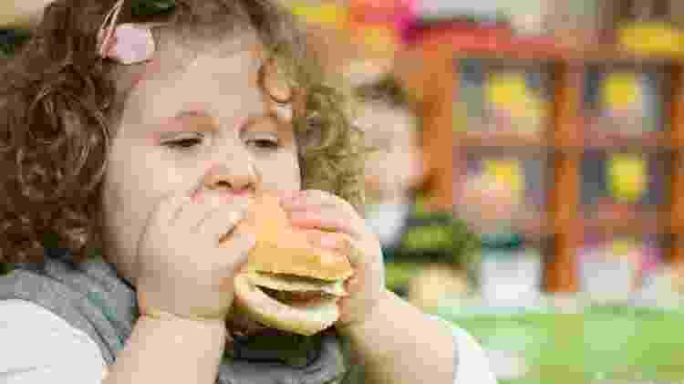 Criança comendo hambúrguer/ obesidade infantil  - iStock - iStock