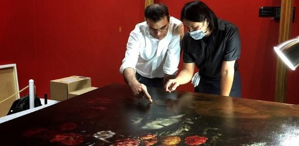 """Funcionário do museu de Taipei e o restaurador Tsai Shun examinam os danos causados à pintura """"Flores"""", de  Paolo Porpora - Reprodução/TST Art of Discovery Co"""