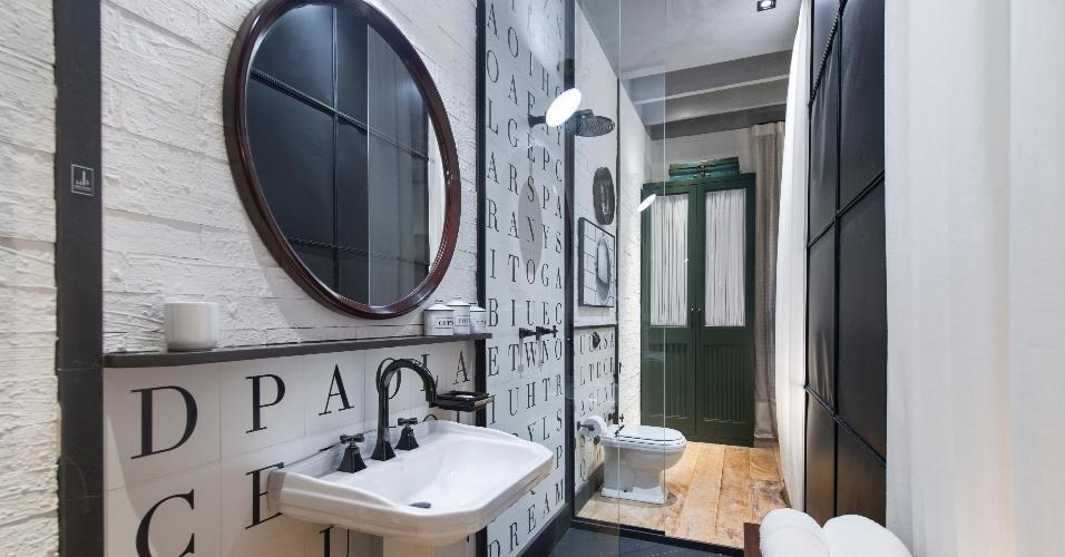 Espelhos circulares com molduras de madeira, parede com azulejos estampados com letrinhas e prateleiras rasas, também feitas de madeira, complementam a decoração do banheiro assinado por Paola Ribeiro, no Loft do Campo