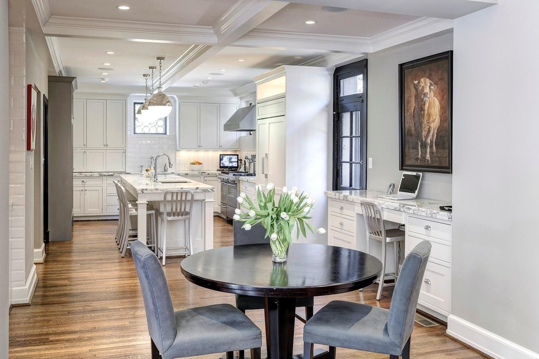 Casa do Obama - Para as refeições do dia-a-dia, a cozinha ampla tem um espaço especial para o café da manhã, com mesa alta (em primeiro plano). Também é possível fazer um lanche rápido na bancada (ao fundo) e usar o computador em um balcão (à dir.). A decoração tem um toque de luxo e sofisticação ao combinar mármore, madeira e acabamentos brancos