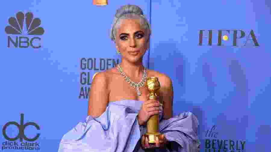 Lady Gaga posa para os fotógrafos no Globo de Ouro com seu prêmio de melhor canção - Mark Ralston/AFP