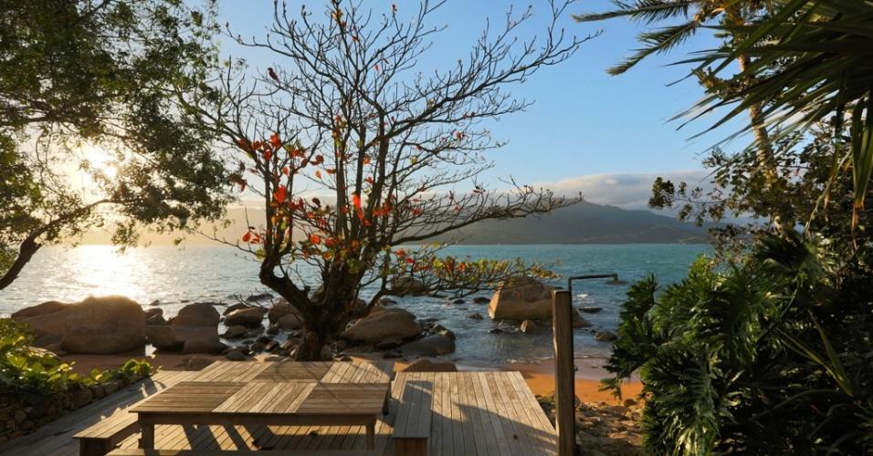 Para o jardim com 2.000 m² de uma casa em Ihabela, litoral norte de São Paulo, o premiado paisagista Alex Hanazaki criou um deck de madeira Itaúba que avança sobre a areia e abriga bancos e mesa ladeados por coqueiros, guaimbês e uma árvore chapéu-de-sol, que faz o papel de um grande 'ombrelone', emprestando sua sombra ao descanso e contemplação da bela vista