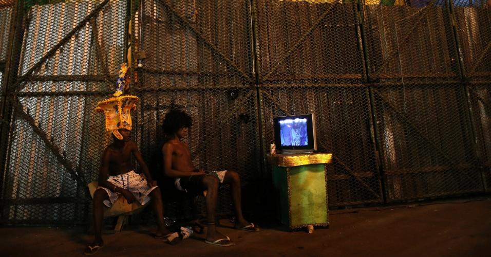 8.fev.2016 - Na dispersão da Sapucaí, garotos assistem na TV o que acontece na avenida