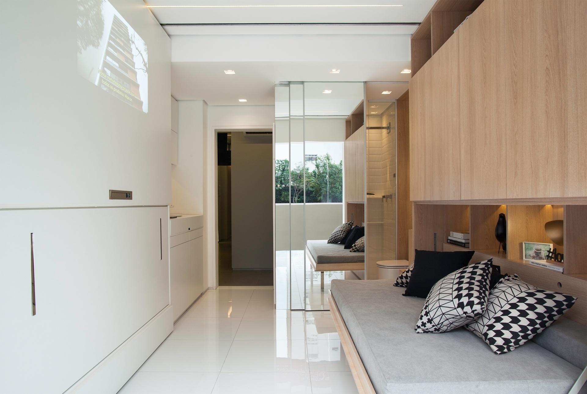 Um dos segredos para a otimização do espaço são os móveis embutidos. Os sofás - da direita (aberto) e da esquerda (fechado) - se unem para formar uma cama de casal. As portas tiveram os puxadores substituídos por recortes na madeira, o que deixa a aparência mais leve e evita enroscos e batidas durante a circulação. O projeto de arquitetura de interiores é da arquiteta Consuelo Jorge