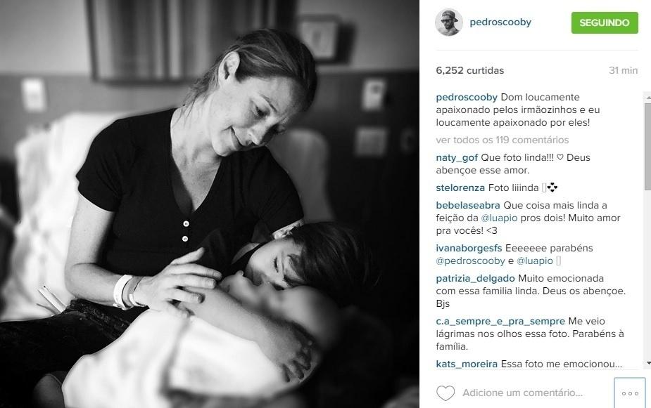 2.set.2015 - Marido de Luana Piovani, Pedro Scooby mostra foto do filho, Dom, abraçando os gêmeos recém-nascidos enquanto é observado carinhosamente pela atriz.