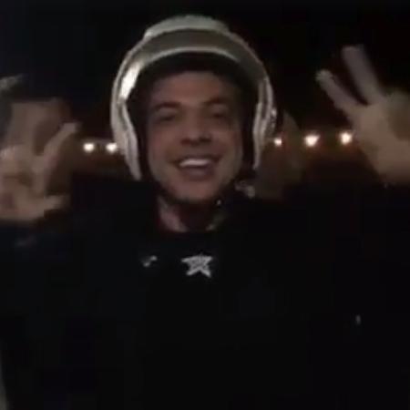Safadão chega ao local da apresentação na garupa da moto e usando o capacete da Guarda Municipal de Limoeiro - Reprodução