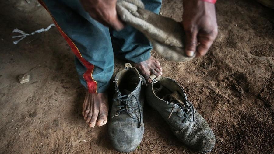 Francisco Rodrigues dos Santos, resgatado de situação de trabalho escravo tira o sapato no assentamento em Nova Conquista em abril de 2015 - Mario Tama/Getty Images
