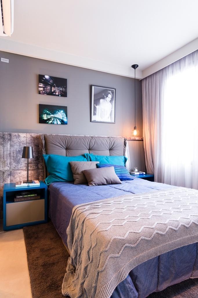O quarto do casal tem cabeceira tipo almofadão e a decoração segue a ideia dos degradês em cinza e azul que rege os interiores do apê. As cortinas, em linho leve e claro, fica embutida na sanca, onde também foram inseridas fitas LED. O tapete cinza escuro é Clatt. O apartamento Alvorada tem projeto de interiores assinado pelo escritório Suite Arquitetos