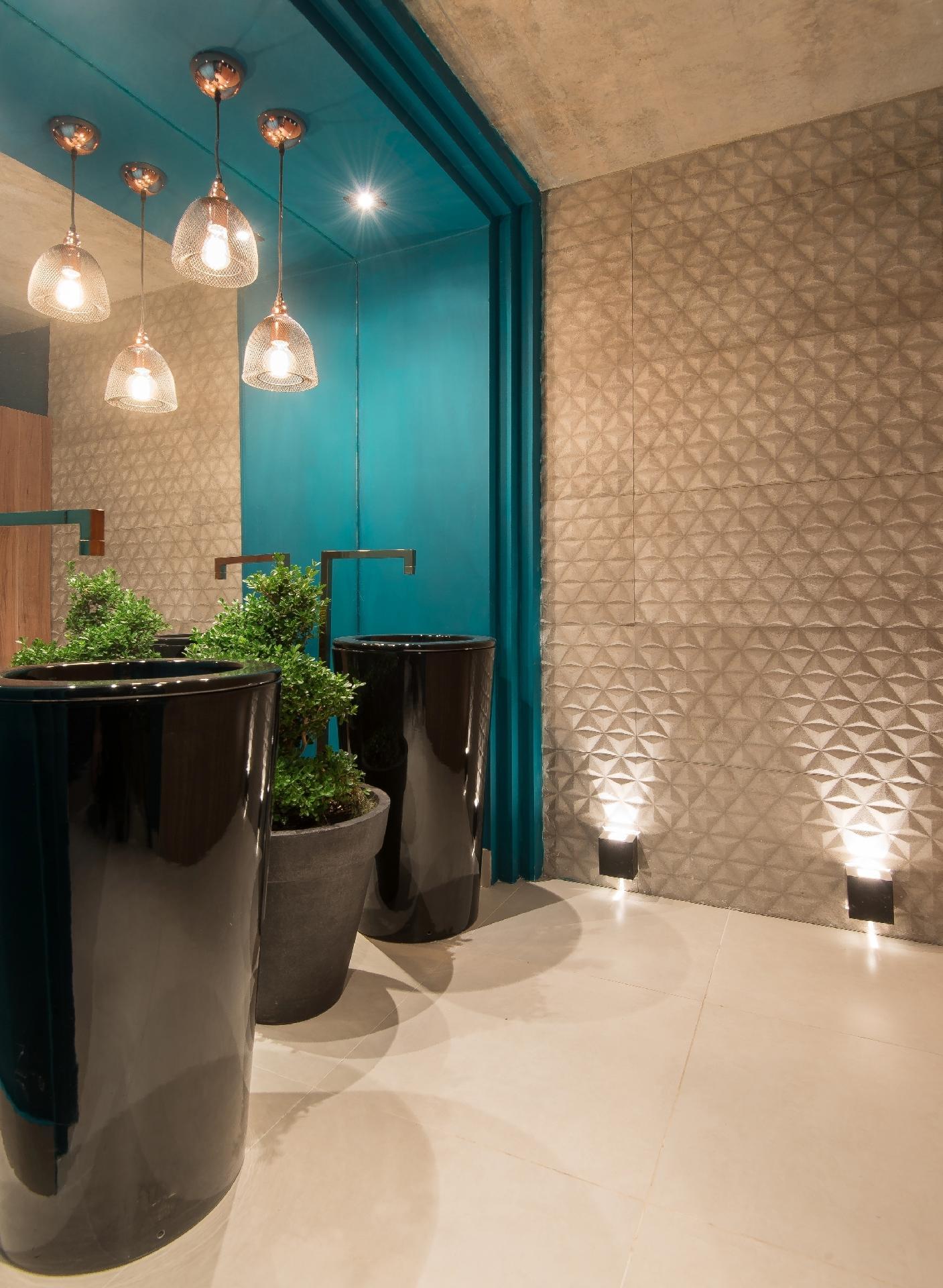 Casa Cor MS - 2016: o Banho Público, projetado por Paula Magalhães, pode ser usado pelos visitantes da mostra. O teto de concreto é combinado a uma estrutura turquesa, que delimita e emoldura espelhos e cubas. À direita, uma parede texturizada é evidenciada pela iluminação