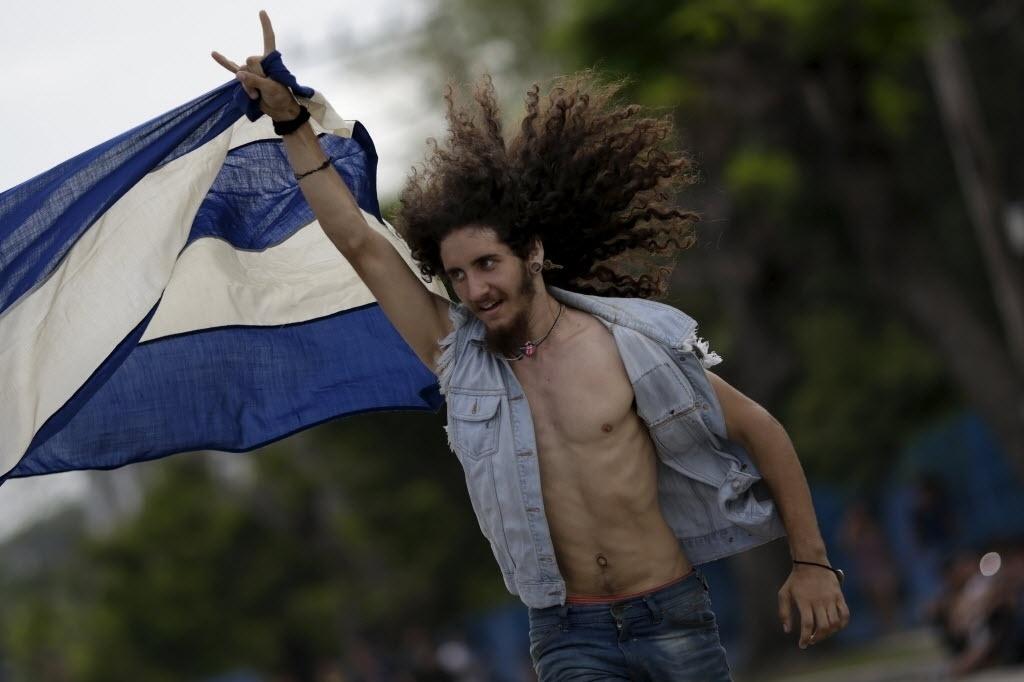 25.mar.2016 - Estudante de música que se autodenomina Rocky balança bandeira de Cuba antes do show gratuito dos Rolling Stones na Cidade Esportiva em Havana