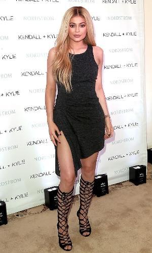 Kylie Jenner usa botas até o joelho com vestido preto e fenda
