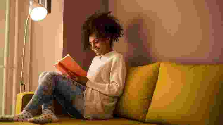 Mulher lê livro em sofá; leitura; canto da leitura - Getty Images/iStockphoto - Getty Images/iStockphoto
