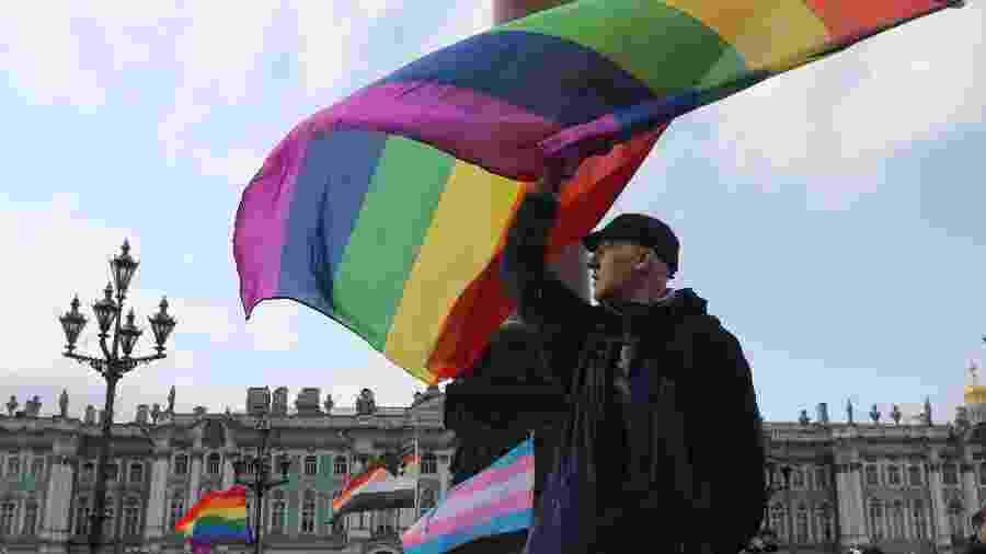 Homem segura bandeira LGBT durante protesto na Rússia - Anton Vaganov/Reuters