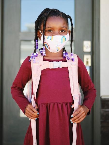 Menina indo para escola com máscara coronavírus - iStock