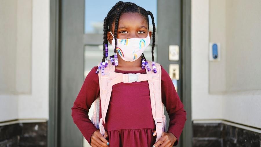 Menina indo para escola com máscara de proteção contra o coronavírus - iStock