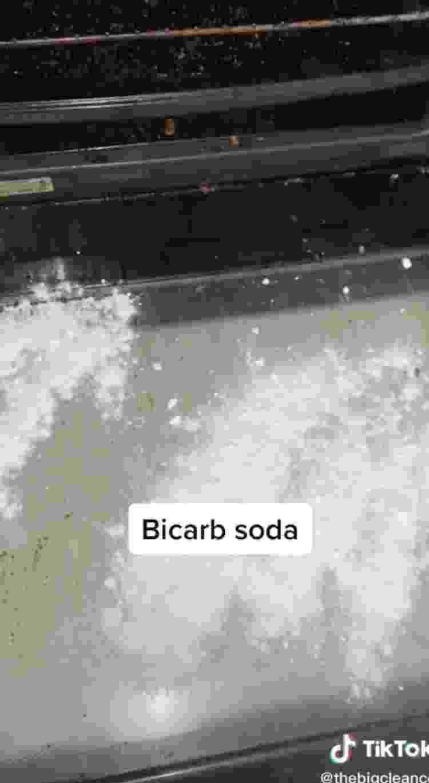 Bicarbonato de sódio espalhado na porta do forno para a limpeza - Reprodução/TikTok - Reprodução/TikTok