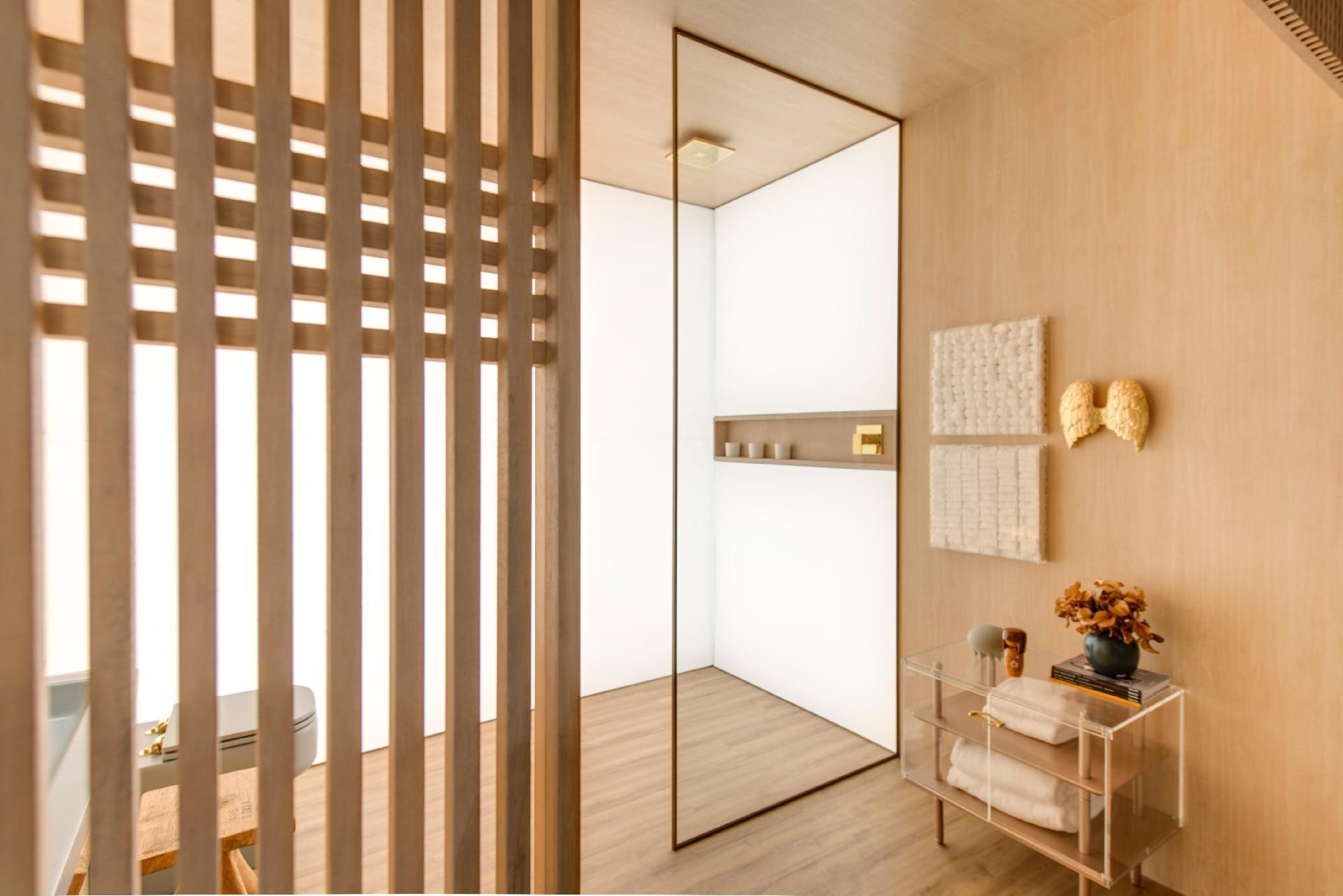 No espaço dedicado ao banho no apê com inspiração japonesa Shoji 04, desenvolvido pelo escritório Yamagata Arquitetura, a iluminação foi instalada por trás da superfície leitosa. Os metais são dourados, enquanto os quadros pendurados na parede foram recheados de algodão