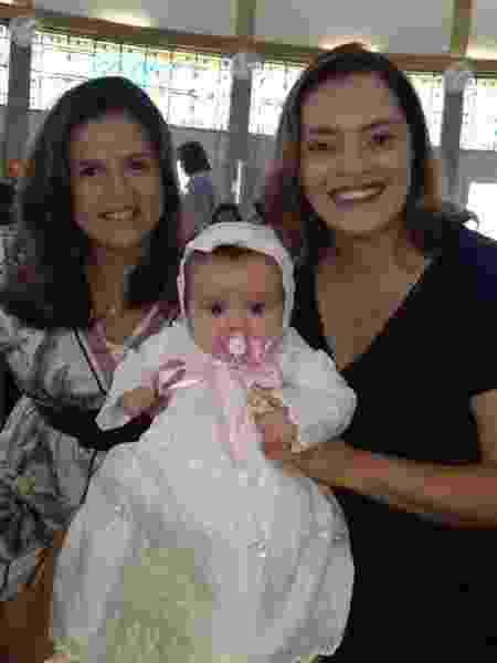 Gislene, com a mulher, Amanda, e a filha Manu, no dia do batizado da criança na Igreja Católica  - Arquivo pessoal