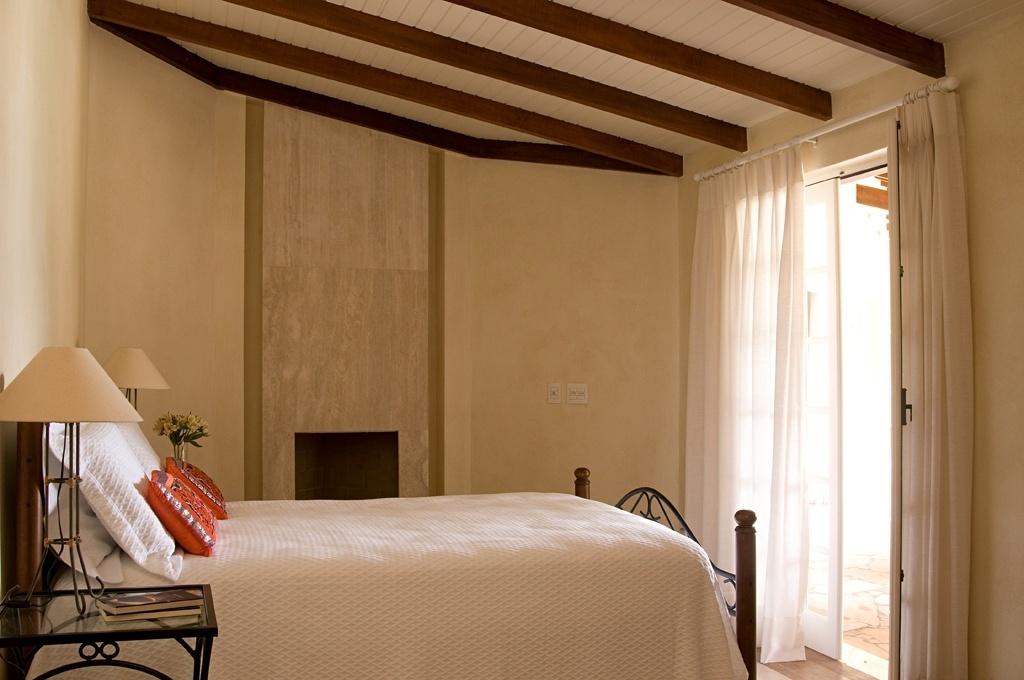 Neste quarto de casal de uma casa de campo, a lareira (ao fundo) aquece o cômodo nos dias mais frios. E o forro de madeira aumenta a sensação de aconchego, no projeto do escritório Díptico Design de Interiores