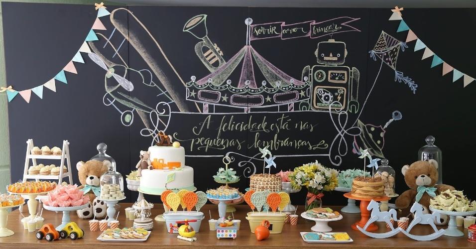 Nesta festa com tema brinquedos antigos, o painel atrás da mesa do bolo foi feito com a técnica