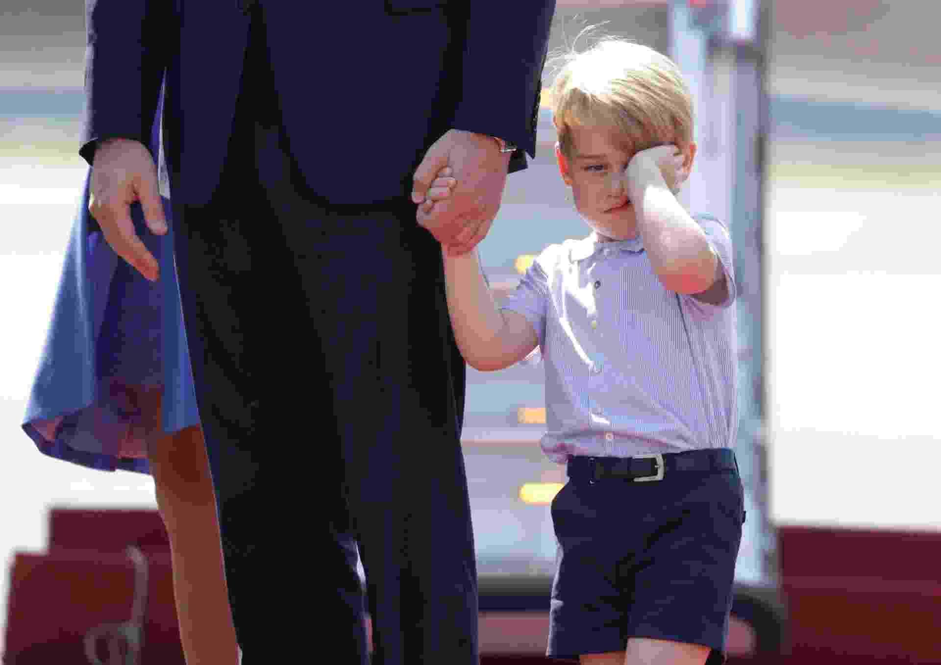 Sonolento, príncipe George esfrega o rosto ao desembarcar com os pais na Alemanha - AFP PHOTO/POOL/Kay Nietfeld