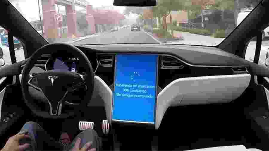 """Imagem de reprodução mostra carro da Tesla operando em modo semi-autônomo; tela de atualização do Windows na central multimídia é """"licença poética"""" de UOL Carros, para mostrar como atualização (não) deve funcionar - Arte UOL Carros/Reprodução"""