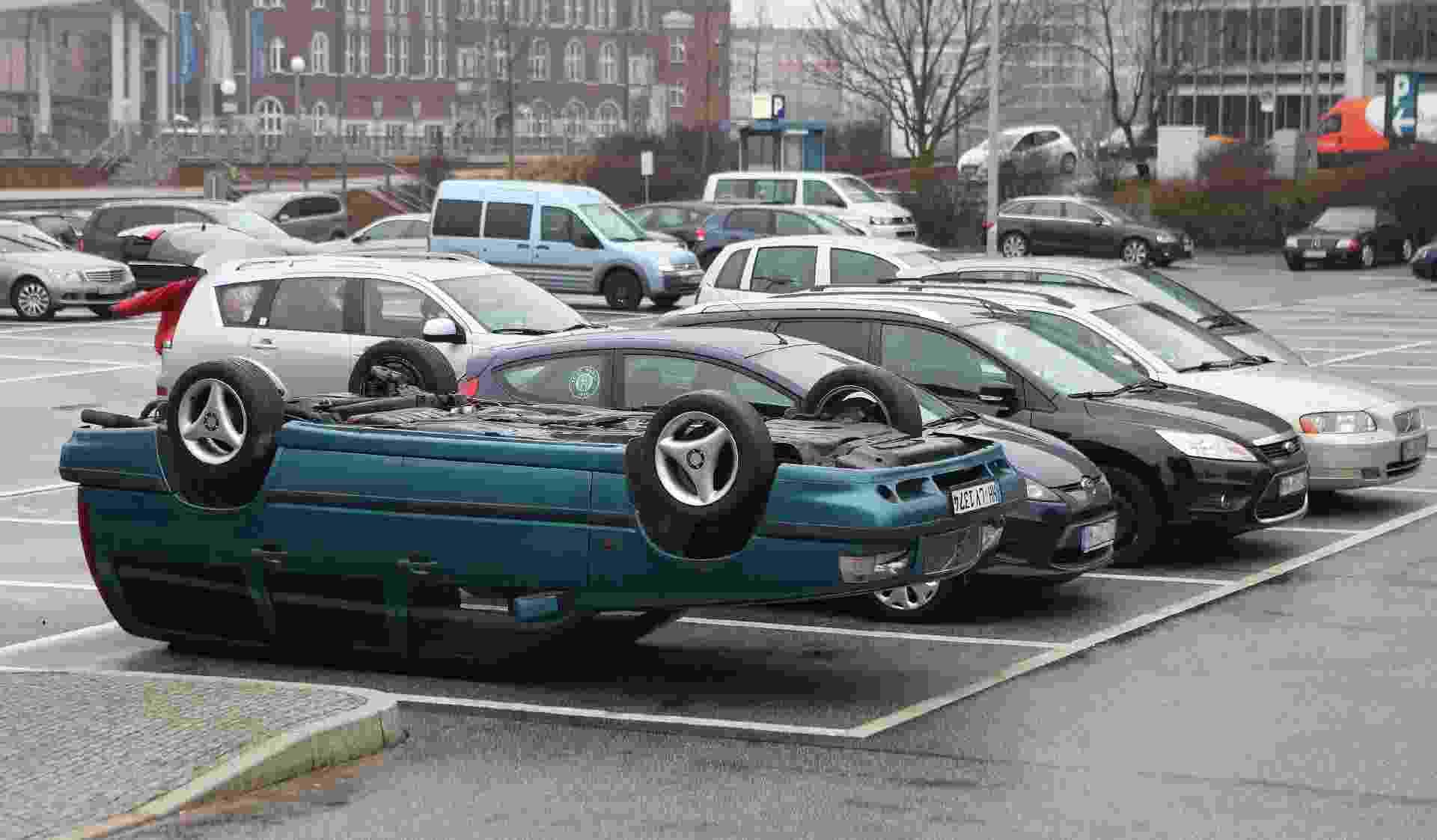 Carro estacionado ponta-cabeça - CHRISTIAN CHARISIUS/AFP