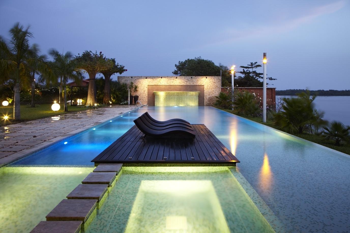Esta piscina luxuosa conta com uma cascata (ao fundo), um deck com espreguiçadeiras e vista para a paisagem natural da cidade de Assinie-Mafia, na Costa do Marfim. Projetada pelo escritório Koffi & Diabaté Architectes, a casa com 833 m² foi concluída em 2007