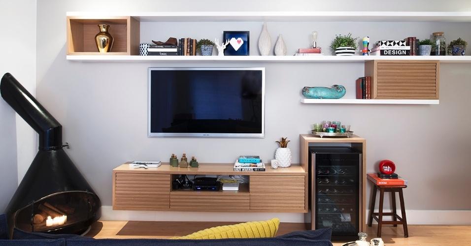 O espaço de TV tem lareira Construflama e adega climatizada, além da marcenaria em tons claros, executada pela Lanzili. A iluminação focal, intimista, fica inserida no rebaixo de gesso, o que aumenta o aconchego. O projeto de interiores é do escritório DN2 Arquitetura