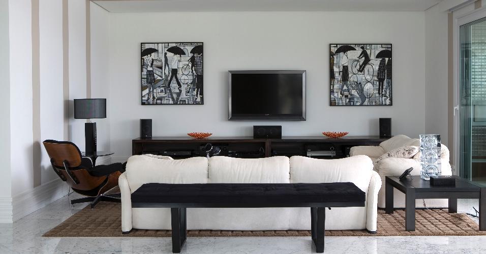 Em tons neutros, a sala de estar é um dos ambientes que compõem o living da casa em Jurerê Internacional, em Florianópolis (SC). O espaço conta com piso de mármore Carrara, sofás brancos e móveis de apoio escuros. O projeto é assinado pelo escritório Maganhoto e Casagrande